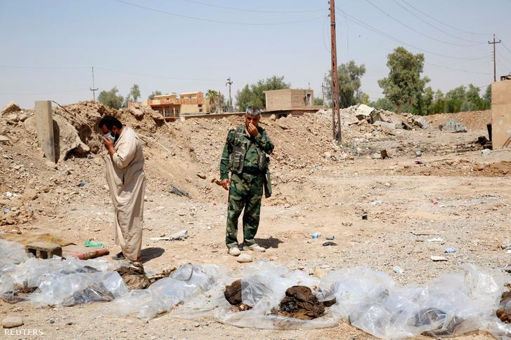 2014-es fotó, amin a tömegsírból kivett testek felett állnak a katonák Sulaiman Pekben, Irakban