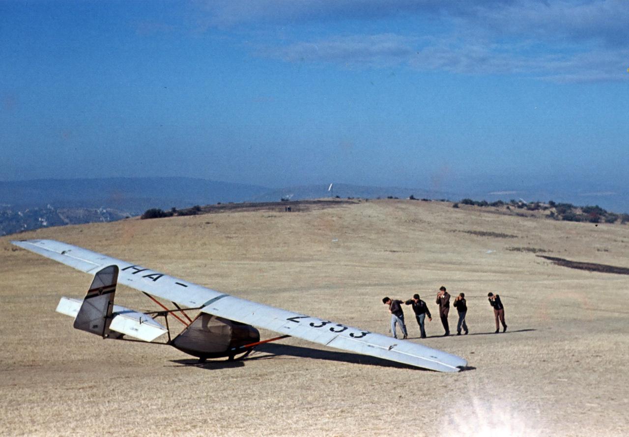 A gumikötelet feszítik ki a Rubik R-07b Vöcsök kilövéséhez a Hármashatár-hegy régi repülőterén, 1960.                         Uramisten, mennyire izzad a tenyerem, mindig ez van. A Rotteré biztos nem izzad. A srácok kihúzták a csúzlit, Tibibá int, megránt a csúzli, áááá, repülök!