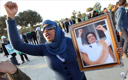 Moammer el-Kadhafi fényképével a kezében kiáltozik egy asszony a Bab al-Azizia támaszponton, Kadhafi parancsnoki központja előtt összesereglett kormánypárti tüntetők között 2011. március 19-én. Ezen a napon öt ország (Egyesült Államok, Franciaország, Nagy-Britannia, Kanada és Olaszország) koalíciója indított támadást Líbia ellen, hogy megbénítsa az észak-afrikai arab ország légvédelmi rendszerét.