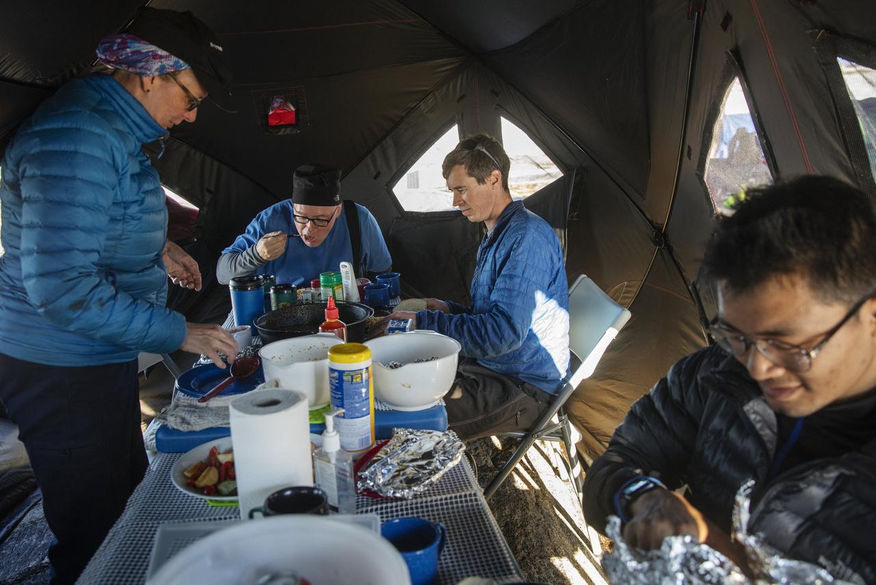 David Holland (középen), Denise Holland (balra), Brian Rougeux és Febin Magar ebédelnek a Helheim-gleccser mellett felhúzott sátrukban.
