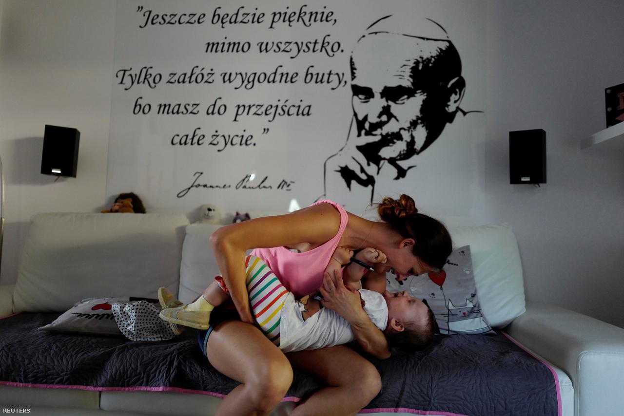 """Monika a lányával, Helenával játszik. A falon II. János Pál képe, alatta idézet: """"Végül majd minden szép lesz. Csak húzz kényelmes cipőt, hiszen előtted áll az egész életed, hogy végigmenj rajta."""" Nem tudni, hogy a pápa vajon a surranóra gondolt-e."""