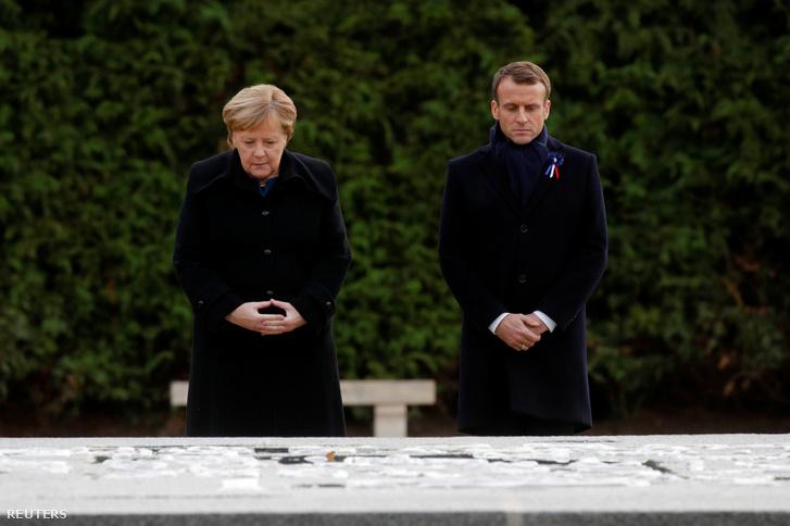 Emmanuel Macron francia elnök és Angela Merkel német kancellár együtt állnak a Clairière de l'Armistice első világháborús emlékműnél, Compiègne-ben 2018. november 10-én