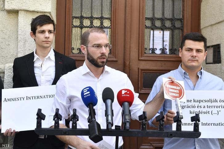 Hollik István a Fidesz-KDNP-frakciószövetség szóvivője (k) sajtótájékoztatót tart az Amnesty International budapesti irodájának helyet adó épület előtt 2018. június 12-én.