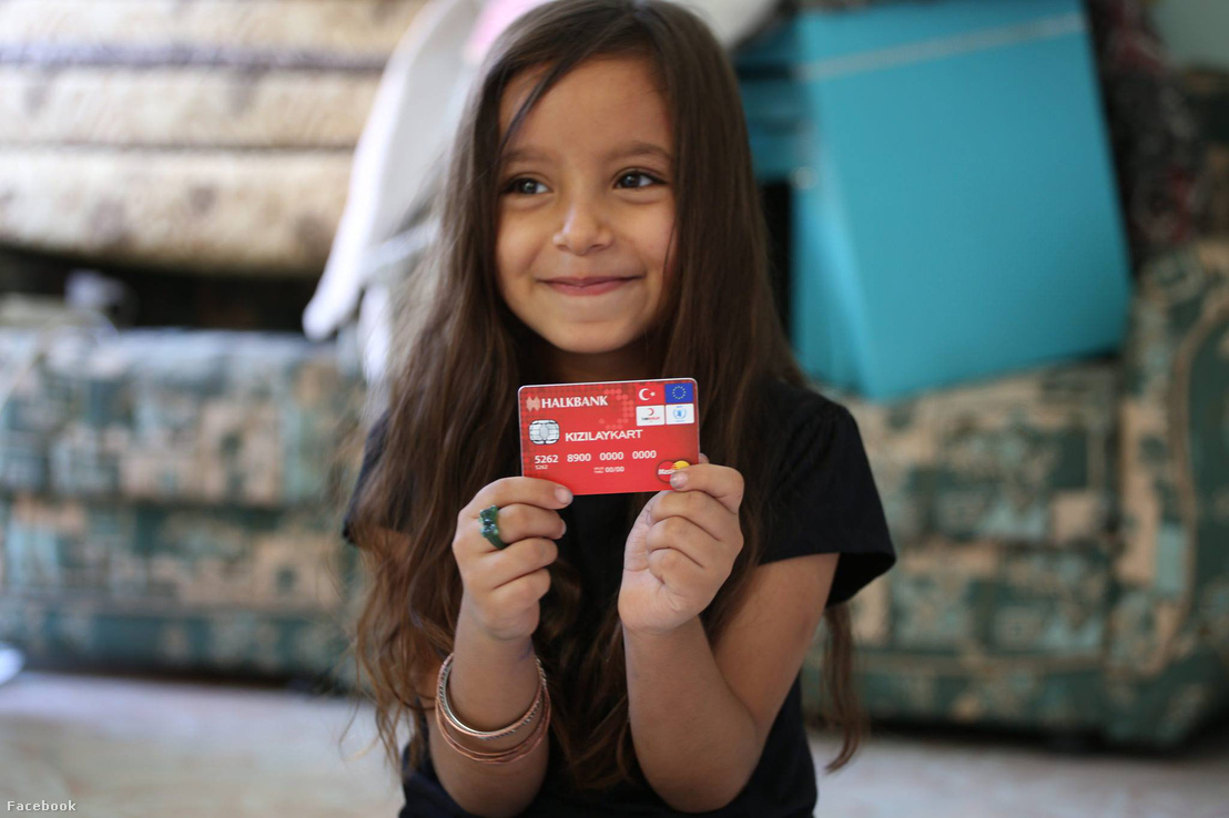 Törökországban tartózkodó menekült kislány tartja a kezében az EU által adott ún. cash assistance kártyát