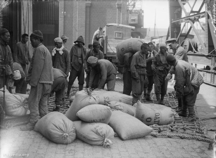 Férfiak a Chinese Labour Corps-tól, brit tisztek felügyelete mellett, zabbal töltött zsákokat raknak egy Boulogne-i teherautóra 1917. augusztus 12-én