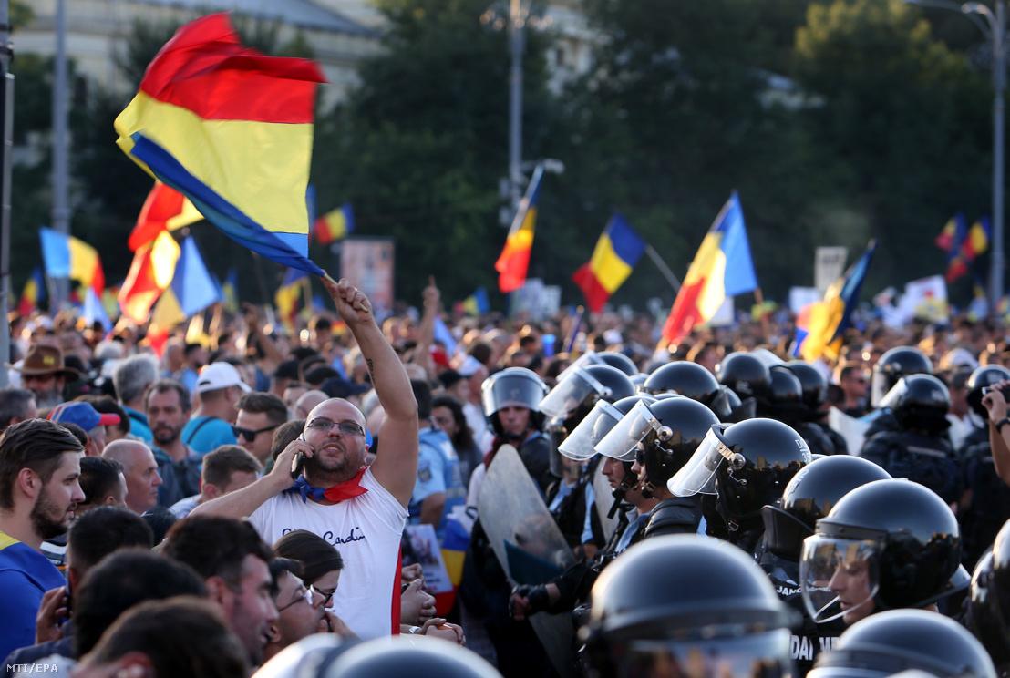 Román zászlót lenget egy férfi a kormány székházát védő rohamrendőrök sorfala előtt a nyári szabadságuk idején külföldről hazatért vendégmunkások a román diaszpóra tagjainak kormányellenes tüntetésén Bukarestben 2018. augusztus 10-én.