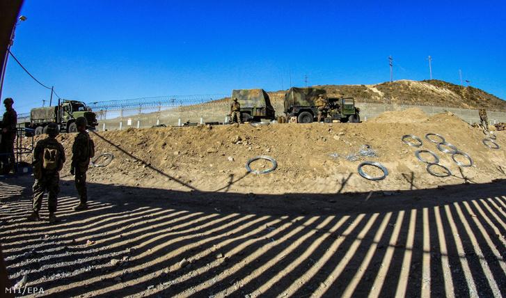 Amerikai katonák pengésdróttal erősítik meg a Mexikóval közös határkerítést az északnyugat-mexikói Tijuanából fényképezve 2018. november 12-én.