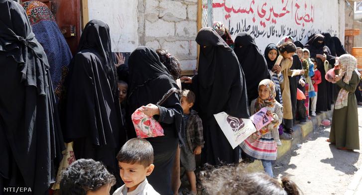 Jemeni asszonyok és gyerekek egy segélyszervezet ételosztására várnak a fővárosban, Szanaában 2018. november 3-án. A 26 milliós népességű közel-keleti országban a lakosság több mint kétharmada nem jut elegendő élelmiszerhez, 11,3 millió ember súlyos nélkülözésnek van kitéve.