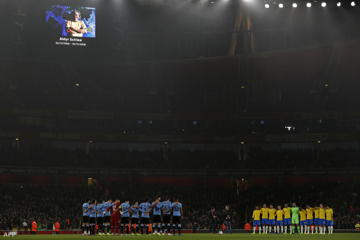 A játékosok egy perc csendet tartanak Aldyr Schlee tiszteletére a Brazília - Uruguay mérkőzés előtt Londonban 2018. november 16-án.
