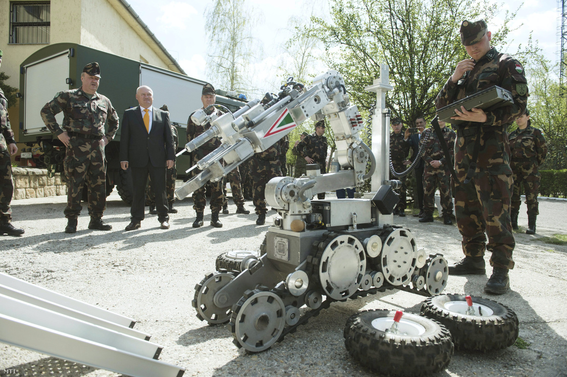 Hende Csaba honvédelmi miniszter és Benkő Tibor vezérezredes honvéd vezérkari főnök (b-j) egy tűzszerész robot mellett a V4-EU Harccsoport többnemzeti tűzszerész szakasza szakharcászati gyakorlatának megnyitóján az MH 1. Honvéd Tűzszerész és Hadihajós Ezred fővárosi laktanyájában 2015. április 13-án.