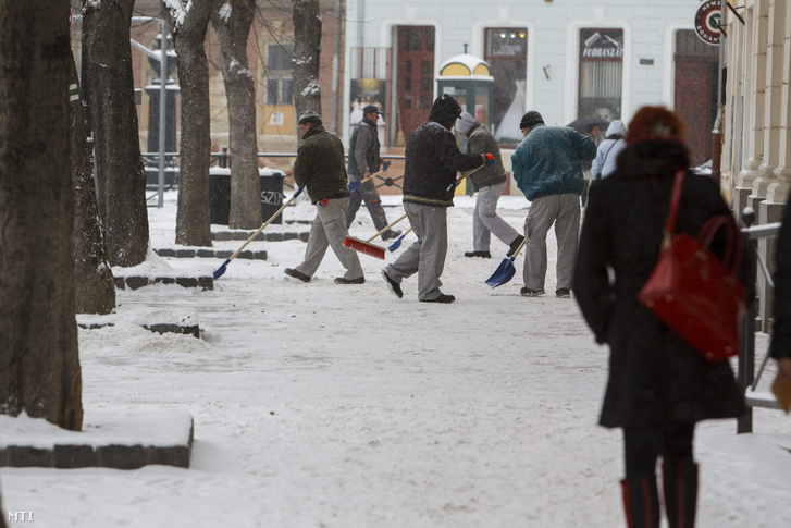 Közmunkások takarítják le a havat a járdáról az Erzsébet téren, Nagykanizsán 2016. január 4-én.
