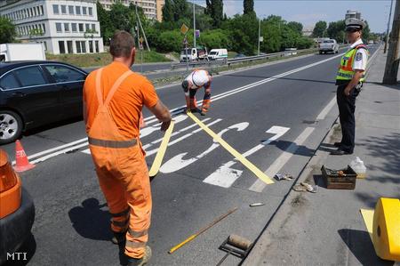 Útkarbantartók leragasztják a buszsávot  a Budaörsi úton. (Fotó: Honéczy Barnabás)