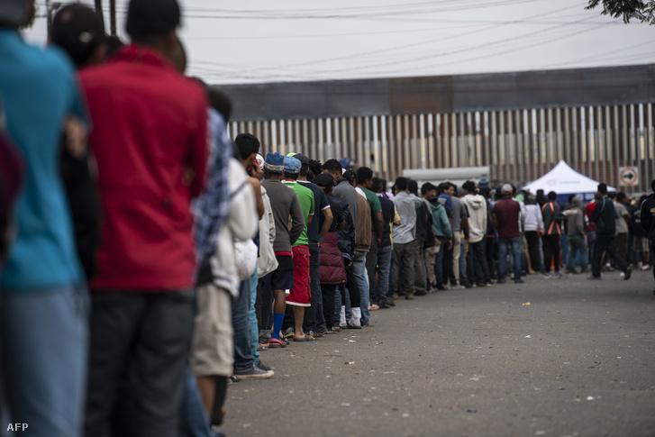 Menedékkérők állnak sorban a mexikói Tijuana (Alsó-Kalifornia állam) városában, a határkerítés közelében 2018. november 24-én