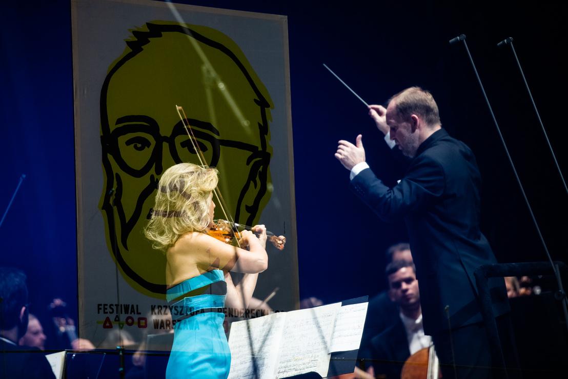 Anne-Sophie Mutter a neki írt Penderecki-hegedűversenyt játssza. Háttérben a mester portréja.