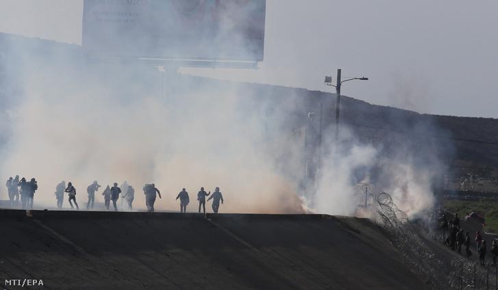 Az amerikai határõrök könnygázt vetnek be hogy visszaszorítsák a határt ostromlókat a mexikói-amerikai határkerítés mexikói oldalán Tijuana városnál 2018. november 25-én.