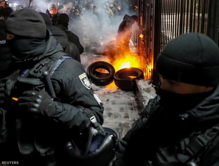 Tüntetők és a nemzeti gárda katonái az orosz nagykövetség előtt, ahol papír hajókat tettek ki és gumit gyújtottak Kijevben 2018. november 26-án