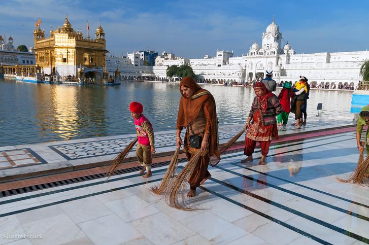 Nők és gyerekek söprik a földet Amritszarban