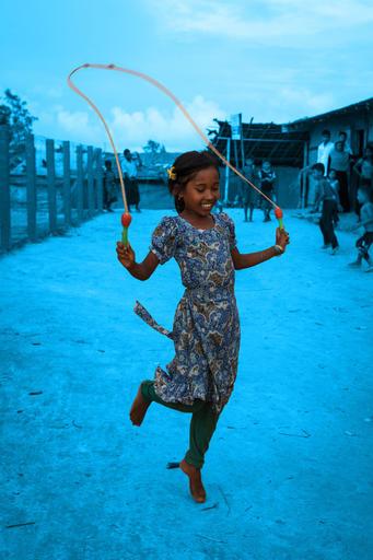 Egy gyerek a borzalmak között is gyerek: ez a rohingya kislány boldogan ugrókötelezik a kerítések árnyékában a Cox Bazaar melletti menekülttáborban.