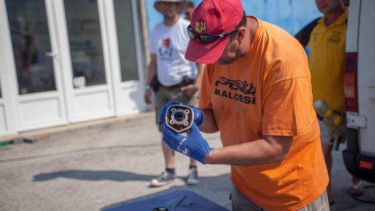 Gépátvétel Gábor verseny végén a megbontott motorok alkatrészeit vizsgálja. A kezében egy Piaggio henger látható, az ötszögletű kialakításról messziről felismerni (a hengert, nem Gábort)