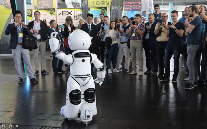Látogatók egy táncoló robotot néznek Európa legnagyobb digitalizációs és innovációs üzleti fesztiválján a hannoveri CeBIT-en 2018. június 12-én.