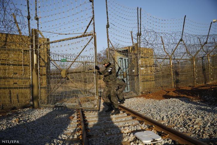Dél-koreai tisztviselőket és szakértőket szállító vonat előtt nyitja meg a kaput egy dél-koreai katona a két Koreát elválasztó panmindzsoni demilitarizált övezetben lévő Padzsunál 2018. november 30-án.