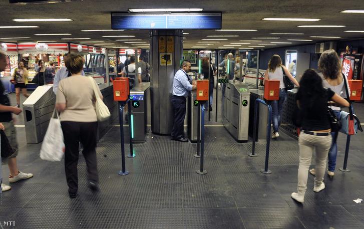 Utasok mennek be az új beléptetőkapun előtérben a régi jegykezelő a Corvin-negyed metróállomáson 2013. június 10-én. Négy különböző beléptetőkaput tesztel a Budapesti Közlekedési Központ (BKK) a főváros M3-as (észak-déli) metróvonalán a Corvin-negyed állomáson.