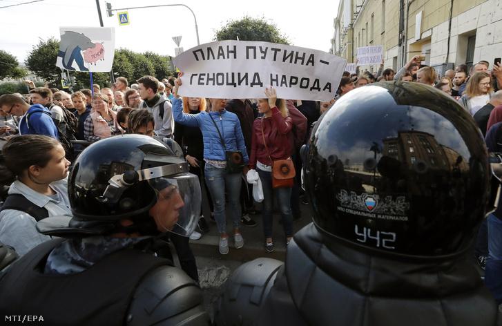 """""""Putyin terve népirtás"""" jelentésű transzparenst visznek tüntetők a nyugdíjkorhatár tervezett emelése ellen tartott szentpétervári tiltakozáson 2018. szeptember 9-én."""