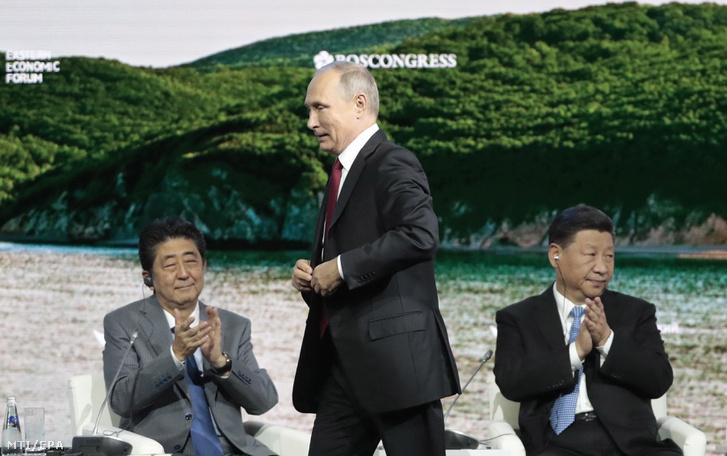 Vlagyimir Putyin orosz elnök a pulpitushoz megy Abe Sindzó japán miniszterelnök (b) és Hszi Csin-ping kínai elnök előtt a vlagyivosztoki Keleti Gazdasági Fórum plenáris ülésén 2018. szeptember 12-én.