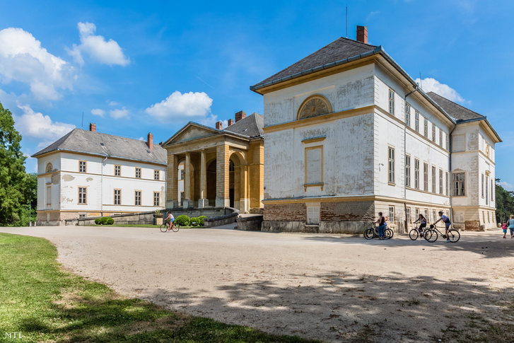 Kerékpáros turisták a dégi Festetics-kastély klasszicista stílusú műemlék épülete előtt 2018. május 20-án.