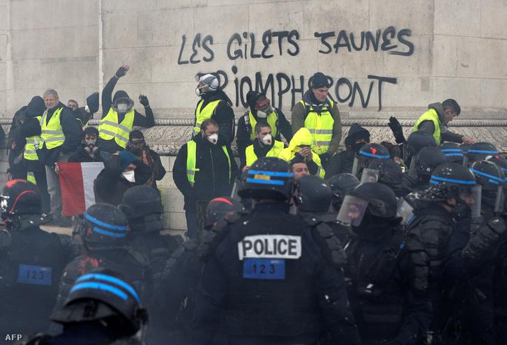 """Sárga mellényesek a párizsi Diadalívnél, amire ráírták """"A sárga mellényesek győzni fognak"""", 2018. december 1-én"""
