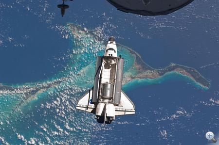 2011. július 10. Az Atlantis űrsikló a Bahamák fölött, nem sokkal a Nemzetközi Űrállomáshoz való csatlakozás előtt. A kép felső részén az ISS-hez dokkolt orosz Progressz teherűrhajó egy kicsi részlete látható.