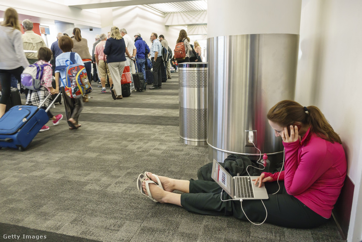 Egy nő tölti a számítógépét és a telefonját egy Los Angeles-i repülőtéren