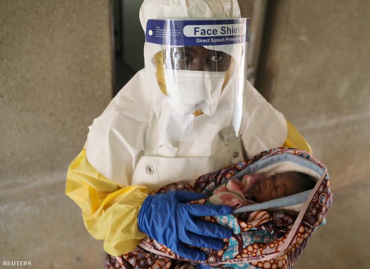 Egy egészségügyi dolgozó kezében tart egy beteg csecsemőt Kongóban 2018. december 6-án.