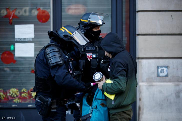 Francia rendőrök ellenőrzik egy tüntető hátizsákját Párizsban 2018. december 8-án