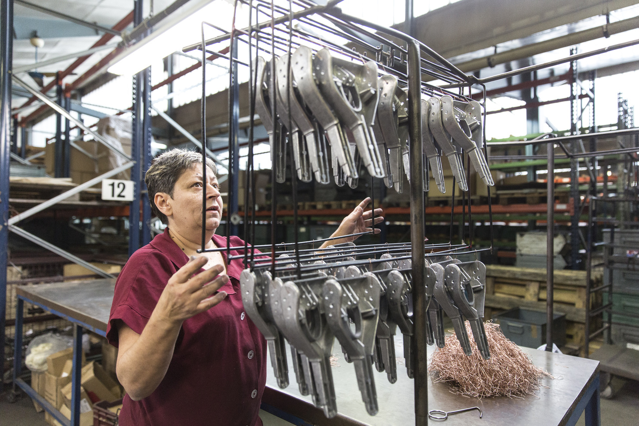 A gyár egyik dolgozója festésre készíti elő a SAX 618 lyukasztógép fogantyúit.