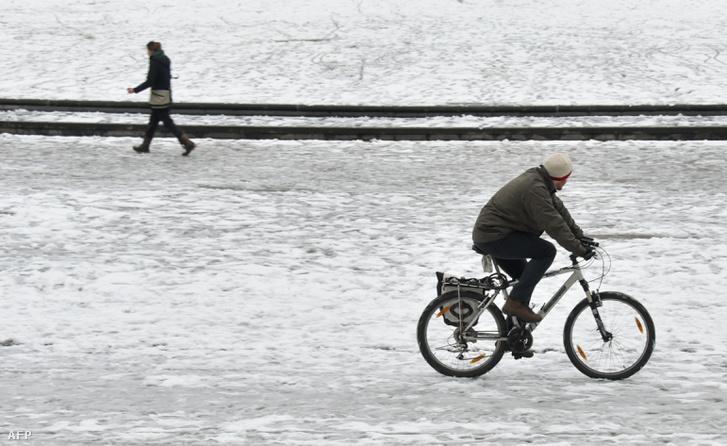 Egy férfi kerékpározik a reggeli hóesésben, Bécsben 2018. február 7-én