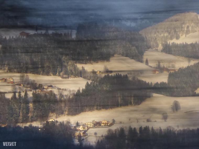 Az osztrák Alpok a lemenő nap fényében, a vonat mellett elsuhanó kopasz fák ágain keresztül fényképezve, kétszázzal száguldó szerelvényről.