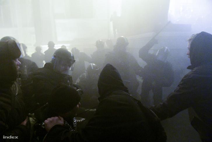 Rohamrendőrök sorfalát próbálják áttörni a tüntetők a budapesti Kossuth téren, a Parlament előtt