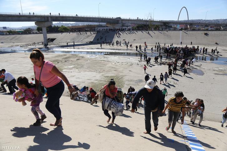 Menekültek próbálnak átjutni az El Chaparral határátkelőnél a mexikói-amerikai határkerítés mexikói oldalán