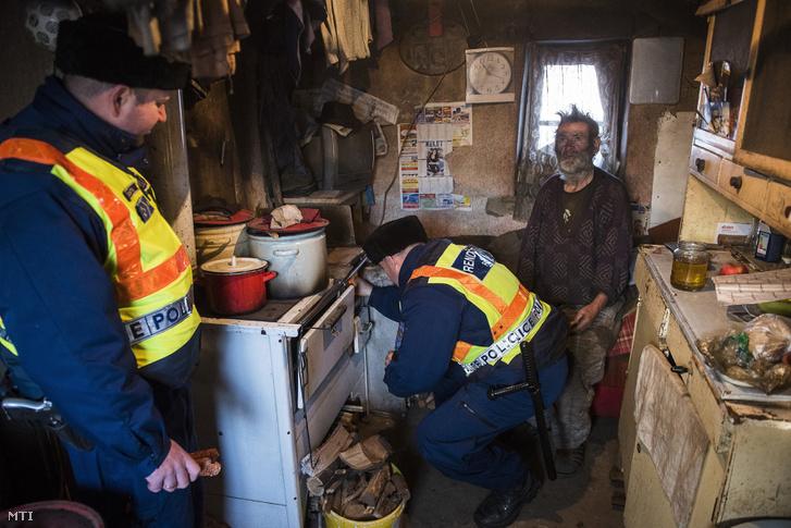 Rendőrök segítenek begyújtani a kályhát egy idős férfi otthonában a Nyíregyházához tartozó Gerhátbokorban 2017. január 6-án. A környéken éjjel -15 Celsius-fokot mértek és napközben sem emelkedett a hőmérséklet -10 fok fölé. A körzeti megbízottak felkeresnek minden olyan idős embert akikről tudják hogy egyedül élnek vagy segítségre szorulnak.