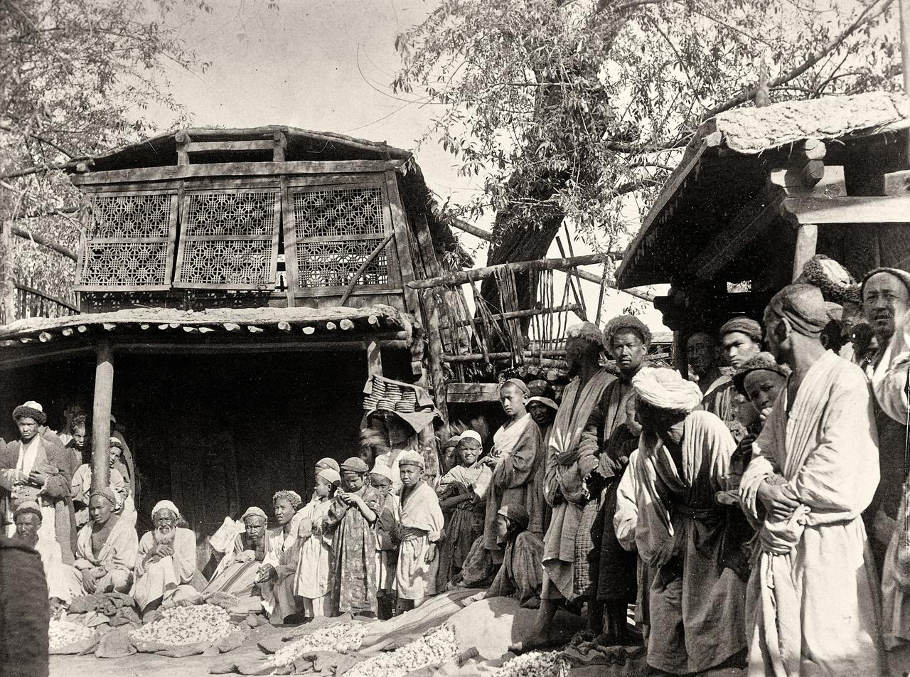 """Bazár a khotani oázisban. Steint egy kicsit John Lockwood Kipling, a Dzsungel könyve írójának apja (és a regény eredeti illusztrátora) """"bolondította meg"""". A Lahore-i múzeum kurátorának gazdag gyűjteménye volt az ősi gandhárai művészet, a közép-ázsiai görög-buddhista szintézis szobraiból; Stein eleinte főleg ezek elterjedését, az indiai-kínai kapcsolat nyomait kereste a Takla-makán sivatag homokja alatt, amihez megkapta Lord Curzon, India alkirálya (és nekünk a trianoni tárgyalásokról is ismerős majdani brit külügyminiszter) támogatását is.Stein volt az első, aki tudományosan felvértezve járta be Kína legvadabb, nyugati perifériáját. Azt a széles vidéket, ami többnyire inkább a senki és a nomádok földje volt, mint a kínaiaké. Ma főleg a digitális rendőrállam által agyonfigyelt ujgurok, korábban fallal távol tartani próbált hsziungnuk, hunok, a krónikákban vérszomjas barbárokként leírt lovasnépek világa volt ez, illetve azoké az oázisoké, egykor virágzó kereskedővárosoké, melyeket a Selyemút tett gazdaggá, majd annak hanyatlása temetett el."""