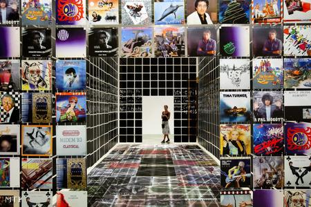 """Érdeklődő néz egy korabeli lemezborítókból álló installációt a Műcsarnok """"Sírba visztek"""" - A Bizottság a Műcsarnokba megy című kiállításán (Fotó: Mohai Balázs)"""