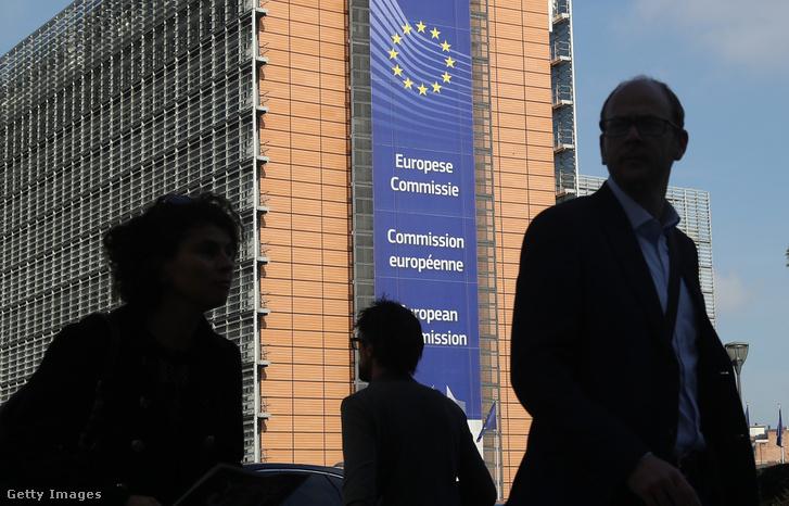 Emberek sétálnak az Európai Bizottság Barleymont épülete előtt, Brüsszelben