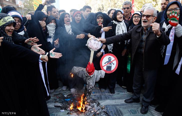 Iráni férfiak Donald Trump amerikai elnök gúnyfiguráját égetik az Egyesült Államok volt teheráni nagykövetségének épülete előtti tüntetésen a nagykövetség elfoglalásának 39. évfordulóján 2018. november 4-én.