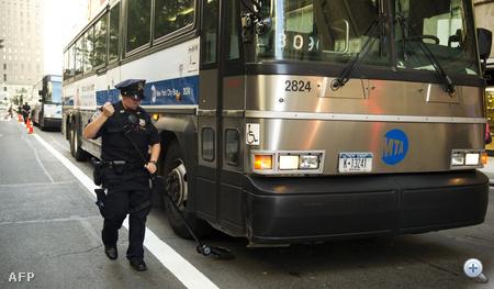 Egy rendőr egy busz alvázát vizsgálja át