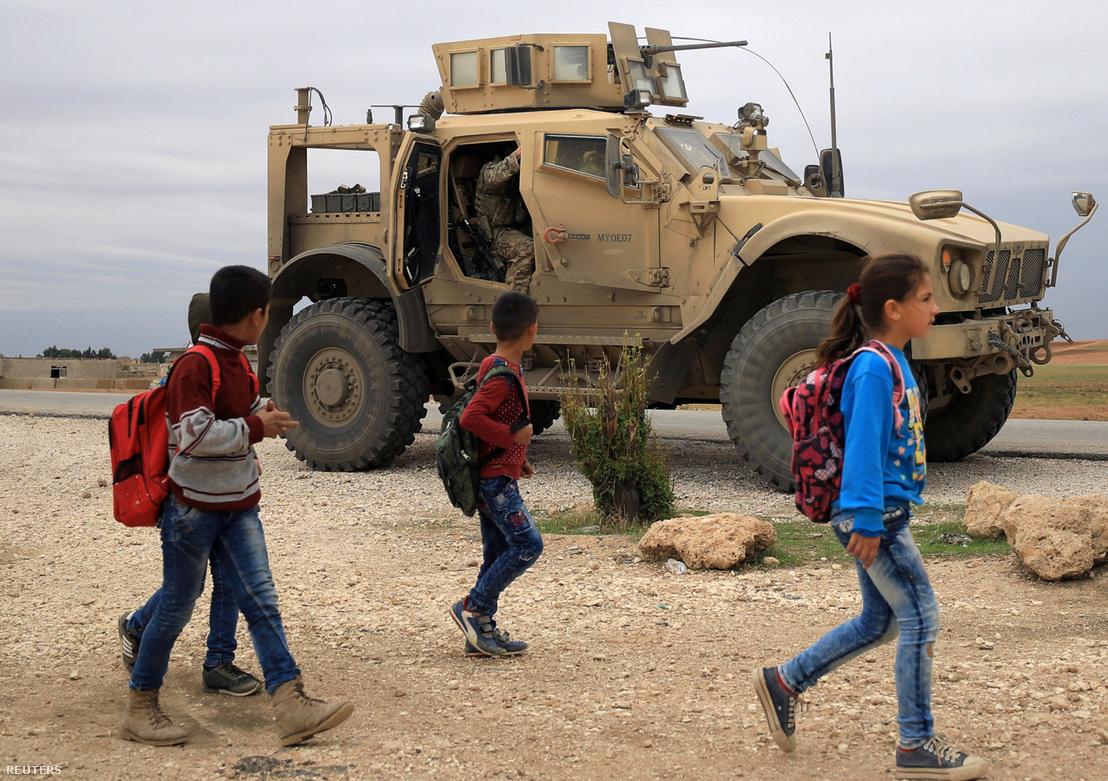 Szíriai iskolások sétálnak a török határ közelében az amerikai katonai járőrök előtt 2018. november 4-én