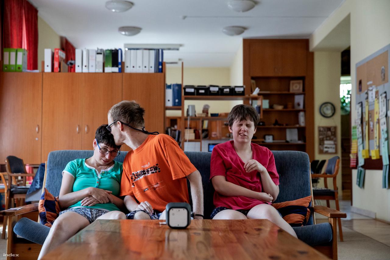 """Edina, Sanya és Kinga várakozik két foglalkozás között az otthon közös nappalijában.Egy lakóotthonnak úgy kell működnie, mint egy nagycsaládnak. A segítők részei ennek a családnak. Nem könnyű összehangolni a közösség, az egyén, a hozzátartozók és a segítők életét. Van, akinek nem sikerül beilleszkednie, és a próbaidőszak végén visszakerül családjához, amely ezután máshol keres megoldást. Ez azonban rendkívül nehéz: csak tíz lakóotthon van, és újakat nem lehet létrehozni, az állam a támogatott lakhatást preferálja. A nagy intézmények sem alkalmasak az autisták szakszerű ellátására, ám épp a nem megfelelő infrastruktúra, az egyedi bánásmód hiánya miatt sokan végül pszichiátriai intézetbe kerülnek. Ez a kényszermegoldás nagy valószínűséggel csak ront az autizmussal élők állapotán.Fenntartható lakóotthonA rendszerszinten megnyugtató finanszírozás egyelőre nem megoldott a rászorulók ellátásában, ez nem csak az autizmussal élők esetében van így. A lakóotthonban mindent az egyesület keretein belül szervezhetnek meg: az étkeztetéstől a készségfejlesztésen át a foglalkoztatásig. A támogatott lakhatásnál alapesetben a szolgáltatásokat külön kell megvásárolni. Az autizmusnál azonban fontos a személyhez kötődés, így ez nem megoldható, ám ilyen esetben a támogatott lakhatásban valójában a működés úgy is megszervezhető, mint egy lakóotthonban. Ráadásul ez már 2–5 fővel is indítható – márpedig a kis létszám kulcsfontosságú lehet az autisták esetében. Az anyagi források biztosítása azonban a támogatott lakhatás esetében nehezebb, ha lényegében lakóotthonként akarna működni. """"A rendszerben akkor lesz rend, ha minden fogyatékos ember a szükségleteinek megfelelő pénzösszeget kap a hátizsákjába, hogy hozzájuthasson a megfelelő szolgáltatásokhoz – mondja Schenk Erika. Attól, hogy az állam ezt elismerje, még messze vagyunk, épp ezért múlik sok az intézményvezetők egyéni kezdeményezőkészségén, hogy előteremtse a működéshez szükséges összeget az állami támogatáson és a lakók hozzájárulásán"""