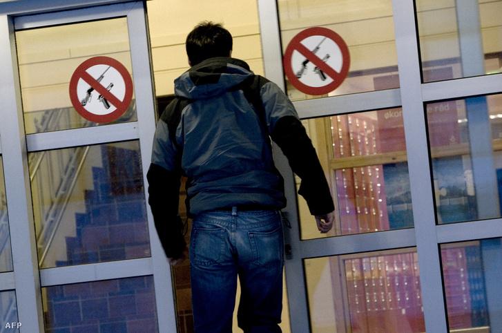 """Ember sétál be egy bank ajtaján Longyearbyen-ben, amelyen """"Tilos a fegyver"""" jel található"""