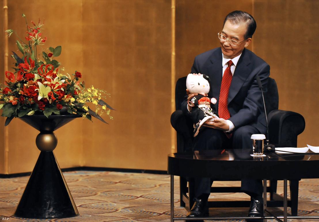 Ven Csia-pao, Kína korábbi miniszterelnöke egy ajándékba kapott Hello Kitty figurával egy japán-kínai kulturális találkozón Tokióban, 2013-ban