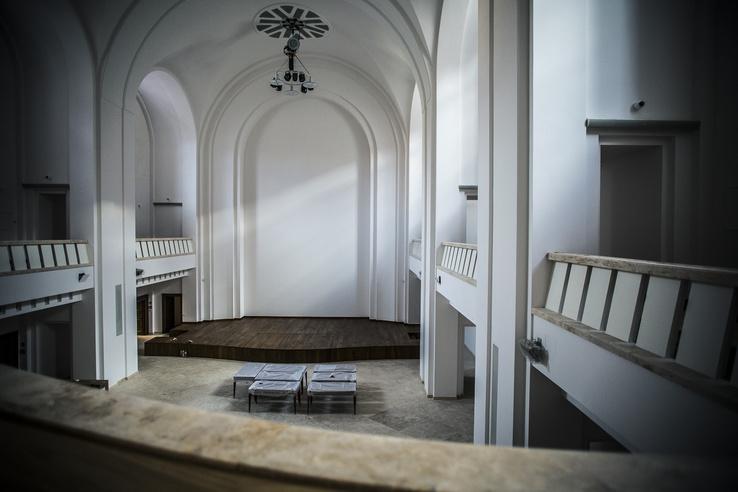 Az egykori kápolna a hátsó karzatról fényképezve. Kétoldalt a kortárs korlátok, a színpad mögött a leválasztott szentély, ahol a könyvtár van